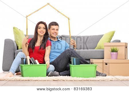 Young couple sitting by a bunch of moving boxes and making a roof over their heads with a tape measure isolated on white background