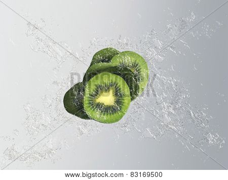 Fresh exotic kiwi fruit with a splash effect and bubbles showing a sliced fruit with pip detail in clear clean water over a graduated grey background