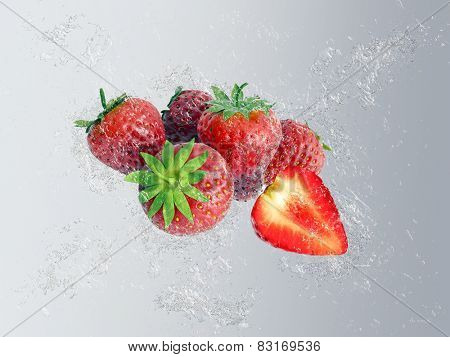 Group of ripe red whole and halved tropical strawberries with dynamic water splash and bubbles over a graduated grey background