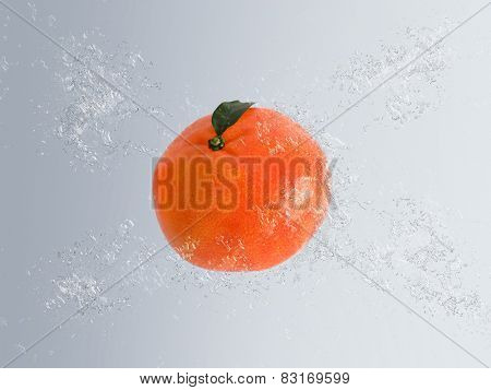 Tasty healthy whole fresh mandarin or clementine falling in water with air bubble effect and copyspace over a graduated grey background