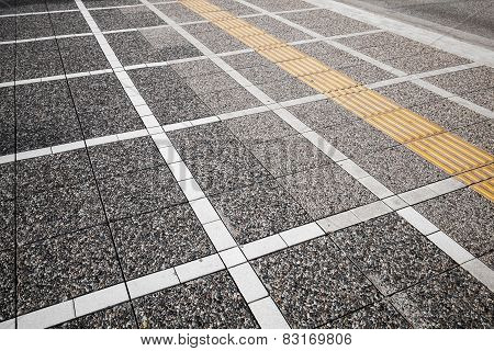 White And Yellow Road Marking Lines On Gray Cobblestone