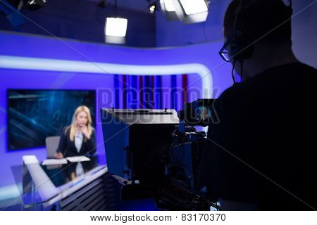 Young beautiful blonde television announcer at studio during live broadcasting.TV NEWS with camera