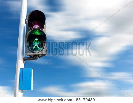 Green Color On The Traffic Light For Pedestrian, Motion Blurred Sky.