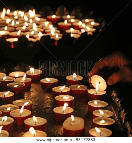 Elderly Faithful Hand Lights A Candle
