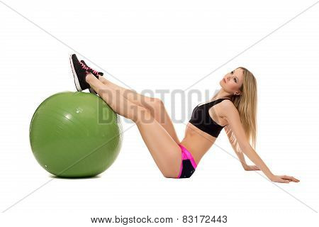 Dreamy sporty girl threw her feet on fitness ball