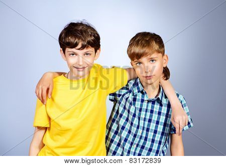 Two boys friends teenagers standing together. Studio shot.
