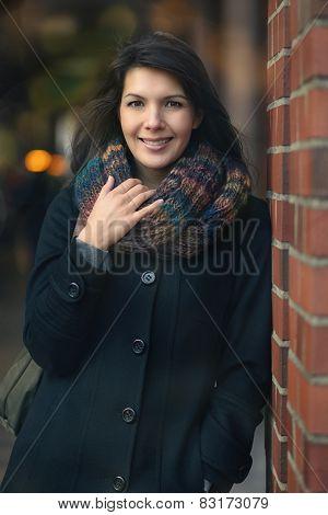 Stylish Pretty Woman Leaning On A Red Brick Pillar