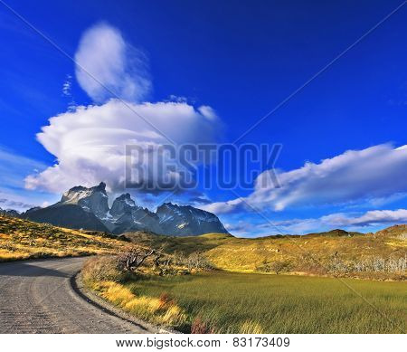 The exceptional beauty of the sunset in the Chilean Patagonia. Fabulous clouds over cliffs Los Kuernos in national park Torres del Paine. The dirt road leads to the mountain range