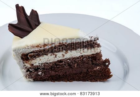 Slice Of Cake With Chocolate And Whipped Cream With White Chocolate Topping On A White Plate