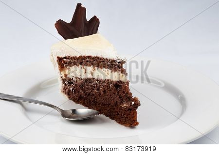 Slice Of Cake With Chocolate And Whipped Cream With White Chocolate Topping And A Spoon  On A White