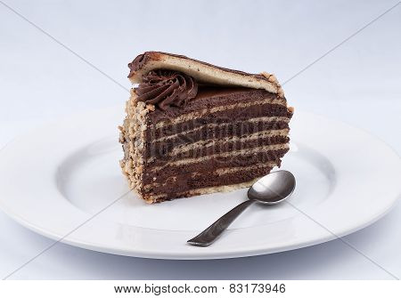 A Chocolate Cake Slice With Chocolate Glossy Syrup Topping And Chocolate Flower And A Spoon On A Whi
