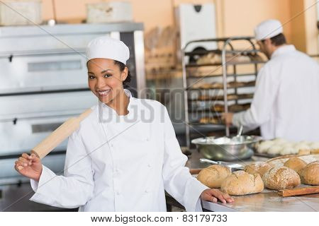 Pretty baker smiling at camera in the kitchen of the bakery
