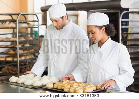 Bakers looking at trays of dough and pastry in the kitchen of the bakery