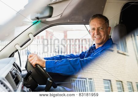 Smiling delivery man driving his van outside the warehouse