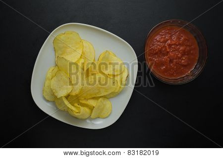 Crisps on a plate and tomato sauce