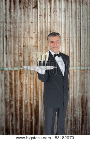 Waiter offering tray with glasses of champagne against wooden planks