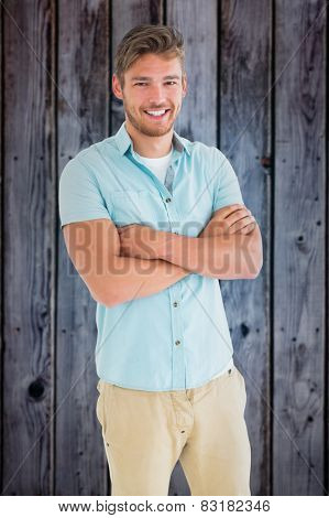 Handsome young man posing with arms crossed against grey wooden planks