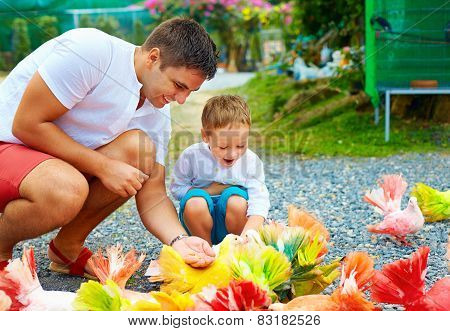 Happy Father And Son Feeding Colorful Pigeons On Animal Farm