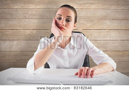 Bored businesswoman typing on keyboard against wooden surface with planks