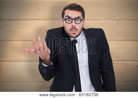 Doubtful businessman with glasses gesturing against bleached wooden planks background