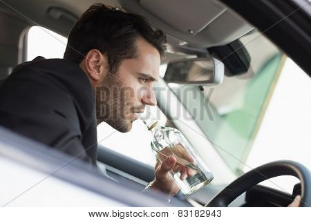Young businessman driving while drunk in his car