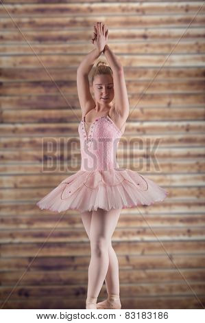 Pretty ballerina in pink against wooden planks
