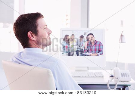 Smiling businessman sitting at his desk against handsome designer sit in his office