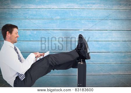 Businessman with feet up on briefcase against wooden planks