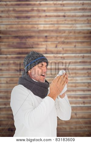 Sick man in winter fashion sneezing against wooden planks
