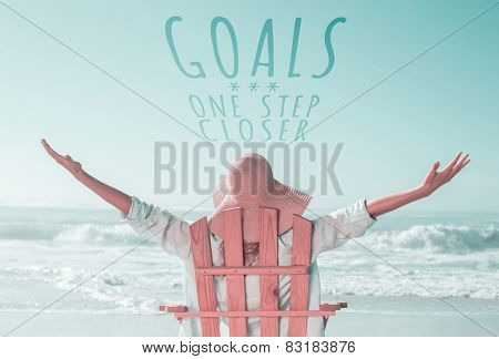 Woman relaxing in deck chair by the sea against goals one step closer