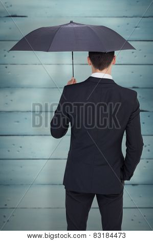 Rear view of businessman sheltering with umbrella against wooden planks