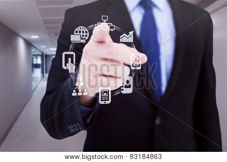 Businessman pointing his finger at camera against college hallway