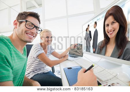 Happy businesswoman posing while her team discussing against cheerful photo editors working on photograph