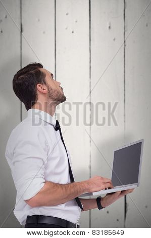 Sophisticated businessman standing using a laptop against white wood