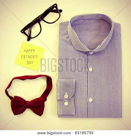 high-angle shot of a table with some mens stuff, such as a plastic-rimmed eyeglasses, a bow tie and a shirt, and a sticky note with the text happy fathers day written in it