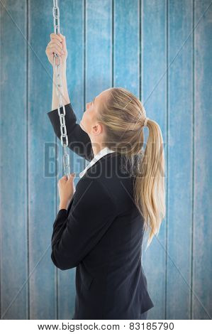 Businesswoman pulling a chain against wooden planks