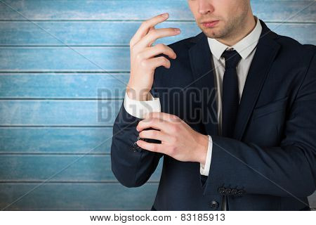 Handsome businessman adjusting his cuffs against wooden planks