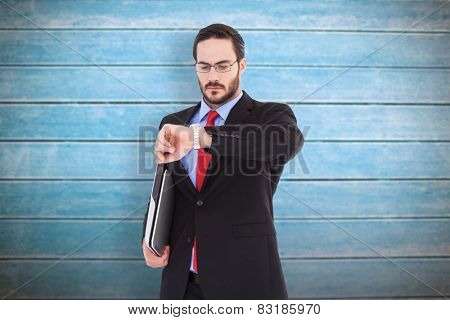 Frowning young businessman checking time against wooden planks