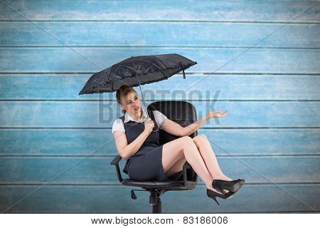 Businesswoman holding umbrella sitting on swivel chair against wooden planks