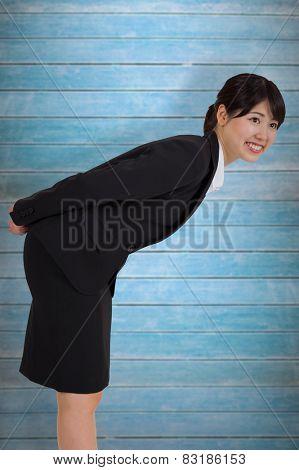 Smiling businesswoman bending against wooden planks