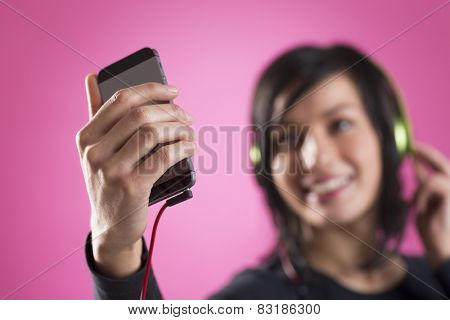 Smiling happy girl enjoying listening to music with headphones and mp3 player, isolated on pink background.