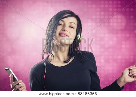 Smiling happy girl enjoying listening to music with headphones and mp3 player while dancing, isolated on pink disco background.