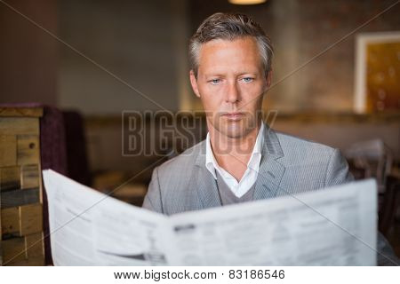 Handsome businessman reading the newspaper at the cafe