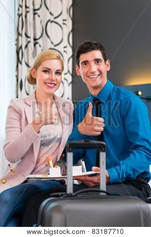 Man and woman eating at arrival in hotel room sweet dessert