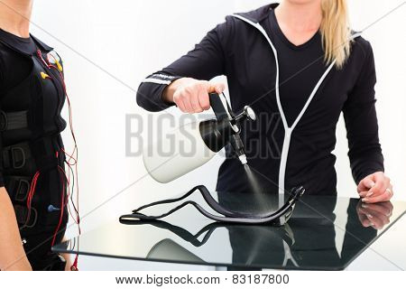 Female coach prepare ems electro muscular stimulation costume