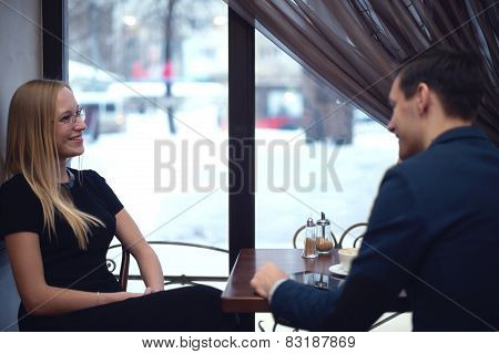 Two young businessmen during lunch in the cafe have a small talk smiling