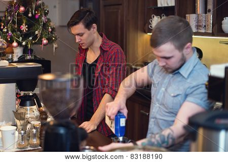 Two hipsters working in a coffee shop making orders cleaning the bar.