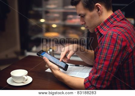 Young  man drinking coffee or tea in the city cafe during lunch time and working on tablet