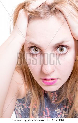 Blonde girl a little worried, holding her face in astonishment