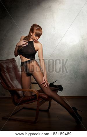 Attractive red hair model with black pantyhose sitting provocatively on armchair - gray background.